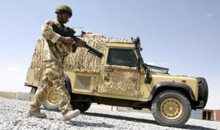 A British soldier walking beside a Snatch Land Rover in Afghanistan