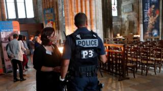 A police officer stands guard during a mass in tribute to priest Jacques Hamel who was killed by two attackers at the Saint Etienne church, in the Cathedral Notre Dame in Rouen, Normandy, France, Wednesday, July 27, 2016.