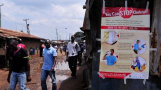 People walk past a kiosk where a poster giving information on how to prevent Cholera is displayed in the Kibera area of Nairobi on May 20, 2015