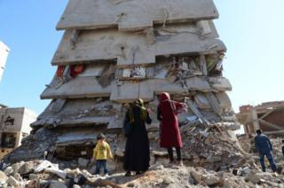 People stand among the rubble of damaged buildings following heavy fighting between government troops and Kurdish fighters in the Kurdish town of Cizre on 2 March 2016