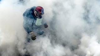 Un manifestante en medio de los gases lacrimógenos.