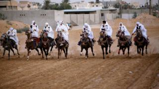 Libyans dressed up in traditional costumes ride horses during a race in Tripoli, Libya, August 19, 2017. Picture taken August 19, 2017.