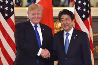 US President Donald Trump (L) shakes hands with Japanese Prime Minister Shinzo Abe (R) before a summit meeting at Akasaka Palace in Tokyo on 6 November 2017.