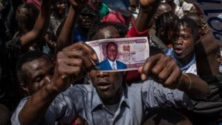 Opposition supporters demonstrate with a fake money with the face of presidential candidate Raila Odinga prior to his mock 'swearing-in' on January 30, 2018 at Uhuru Park in Nairobi, Kenya