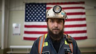 A miner in front of the American flag