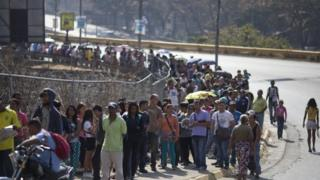 People wait in line to buy products at government regulated prices in Caracas (19 February 2016)