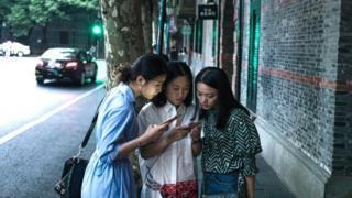 Çinli genç kadınlar cep telefonlarını inceliyor