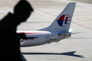 A file picture dated 17 July 2016 shows a passenger walking past a Malaysia Airlines aircraft within a viewing gallery of the Kuala Lumpur International Airport (KLIA) in Sepang, outside Kuala Lumpur, Malaysia.