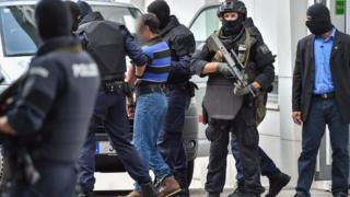 A suspected member of the Islamic state group is led away by Austrian police