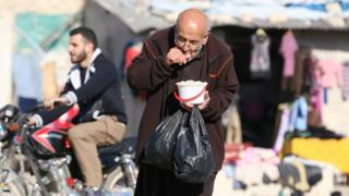A man eats food that was distributed as aid in a rebel-held, besieged area in Aleppo, Syria (6 November 2016)
