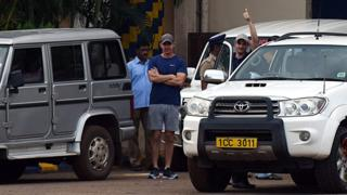John Armstrong (R) gestures next to colleague Nick Simpson (C) as they leave prison in Chennai