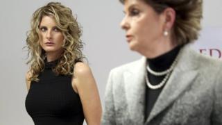 """Summer Zervos (kiri), dengan pengacaranya Gloria Allred, mengatakan bahwa dia membuka tuntutan untuk """"memperbaiki reputasi saya""""."""