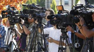Television media cover a news conference in Roseburg, Oregon October 2, 2015