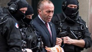 Former prime minister of Kosovo Ramush Haradinaj, center, leaves the court escorted by hooded police officers in Colmar, eastern France