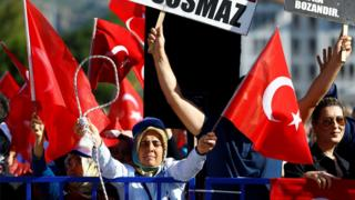 A crowd waves Turkish flags along with brandishes a noose outside the court