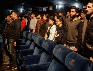 Indian movie goers stand up as national anthem is played at a movie hall before the screening of a movie in Jammu, India, Tuesday, Dec. 13, 2016.