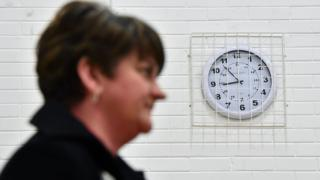 Arlene Foster stands in front of a clock on a wall