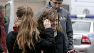 Женщина, плача, разговаривает по телефону около станции метро в Питере