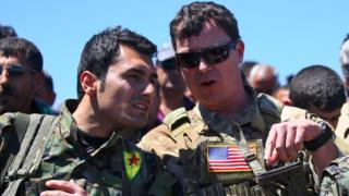 A US officer, from the US-led coalition, speaks with a fighter from the Kurdish People's Protection Units (YPG).