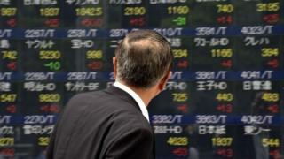 Man looking at share board