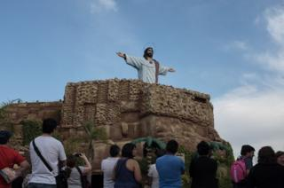Tourists watch Jesus rise