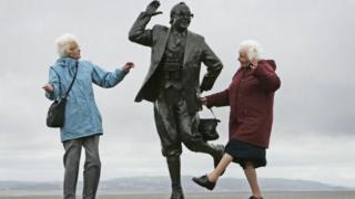 Mulheres dançasm ao lado de estátua