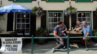 Voters drink beer outside after voting in the White Mill Inn, White Mill village, Carmarthenshire in Wales
