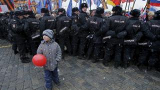 "Boy stands in front of Russian police officers during festive concert marking second anniversary of Russia""s annexation of Crimea in central Moscow"