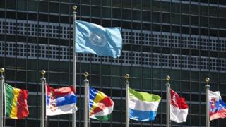International flags fly in front of the United Nations headquarters
