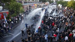 Carros hidrantes tiran agua a los manifestantes en Hamburgo.
