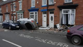 Car on side after crashing into house