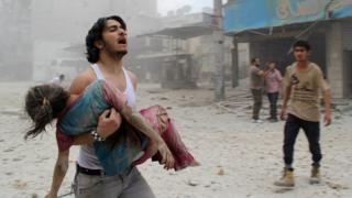 Мужчина несет раненую девочку