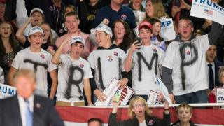 "Supporters wear t-shirts spelling out ""Trump"" at an iowa rally."