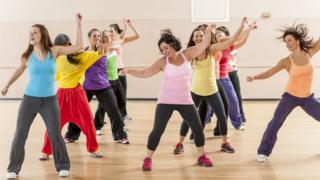 A group of women working out and dancing together during a class in a gym studio.
