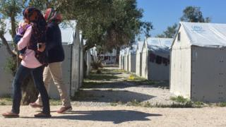 Migrant women walk in front of tents at a camp in Lesbos, Greece