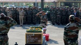An Indian army soldier salutes the coffins of colleagues during a wreath laying ceremony for 17 Indian army soldiers killed in a gunbattle at the army headquarters in Srinagar on September 19, 2016.