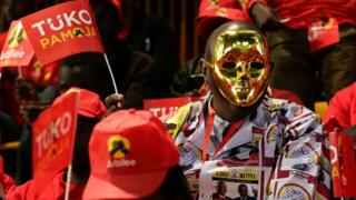 A supporter of Kenya's ruling Jubilee Party supporter dons a mask and a shirt made of canvas with the party leaders pictures printed on at the launch of the manifesto in Nairobi, Kenya, 26 June 2017.