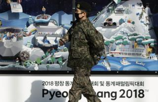 A South Korean soldier walks past the 2018 Pyeongchang Winter Olympic and Paralympic Games PR booth, 5 January 2018