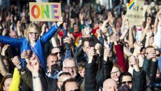 Para pengunjuk rasa saling berpegangan tangan menunjukkan solidaritas.