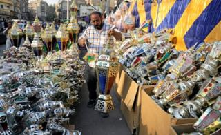 "An Egyptian seller dusts a traditional Ramadan lantern called ""fanous"" at his shop stall ahead of the Muslim holy month of Ramadan"