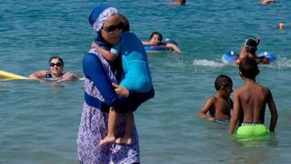 A woman wearing a burkini walks in the water on a beach in Marseille, France. Photo: 27 August 2016