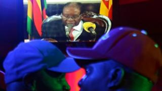 People watch as Zimbabwean President Robert Mugabe addresses the nation on television, at a bar in Harare, Zimbabwe, 19 November 2017