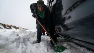 Said, 43, dey remove snow with shovel around im car wey hook for snow, 60km from Azilal city, central Morocco, 05 March 2018 (issued 07 March 2018). Azilal na city wey dey central Morocco, for Atlas Mountains,