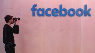 Man takes picture of Facebook logo