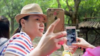 A woman uses her mobile phone to take a picture with panda at the Chengdu Research Base of Giant Panda Breeding in China's Sichuan province