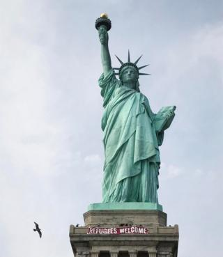 """A giant banner saying """"Refugees Welcome"""" hangs on the pedestal of the Statue of Liberty, New York, 21 February 2017"""