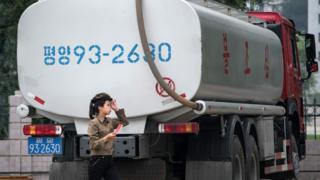 A petrol station worker walks past a fuel truck in Pyongyang