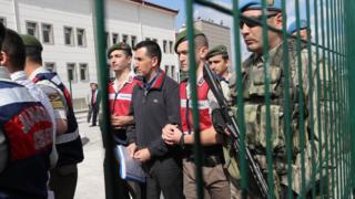 Sanıklar Ankara'da mahkemeye çıkarılırken asker eşliğinde salona götürüldü.