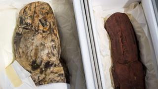 Los dos hallazgos olmecas se muestran en cajas protectoras durante una conferencia de prensa de la Colección Arqueológica estatal de Baviera en Múnich.