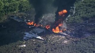 A still image showing a crashed plane in flames in a field, taken from video footage